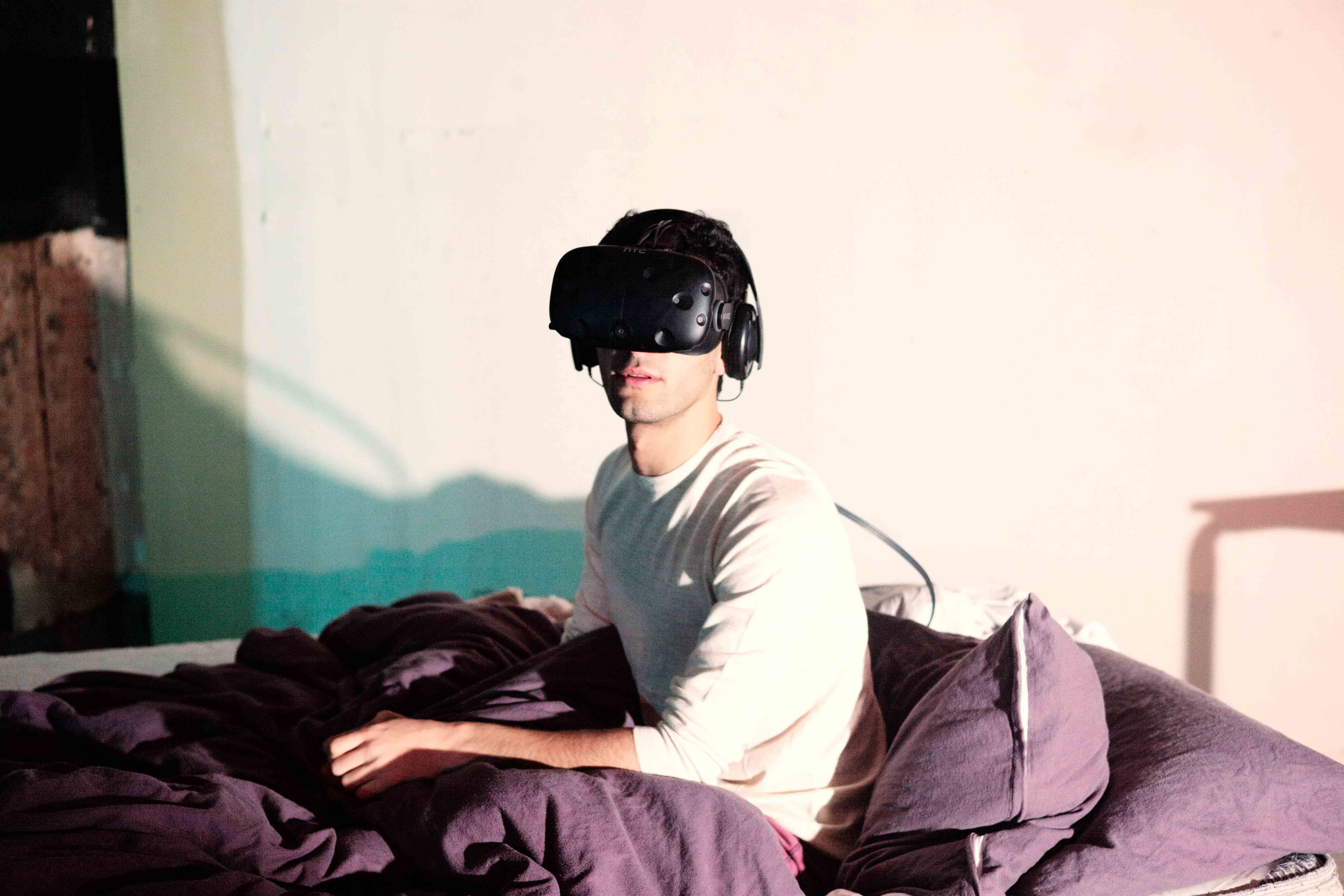 The artist wearing the VR headset, in bed.