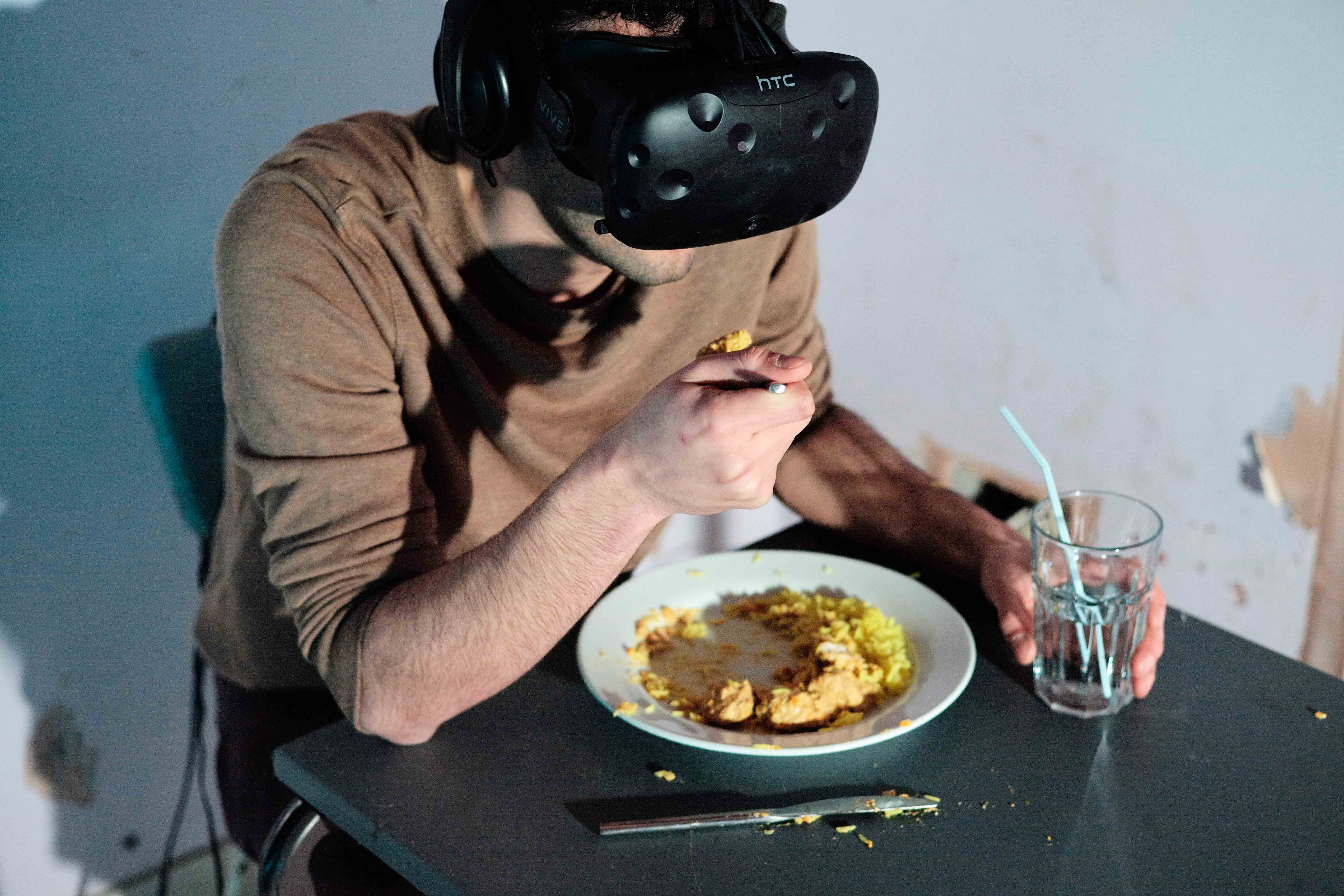 The artist wearing the VR headset eating a curry at the table.
