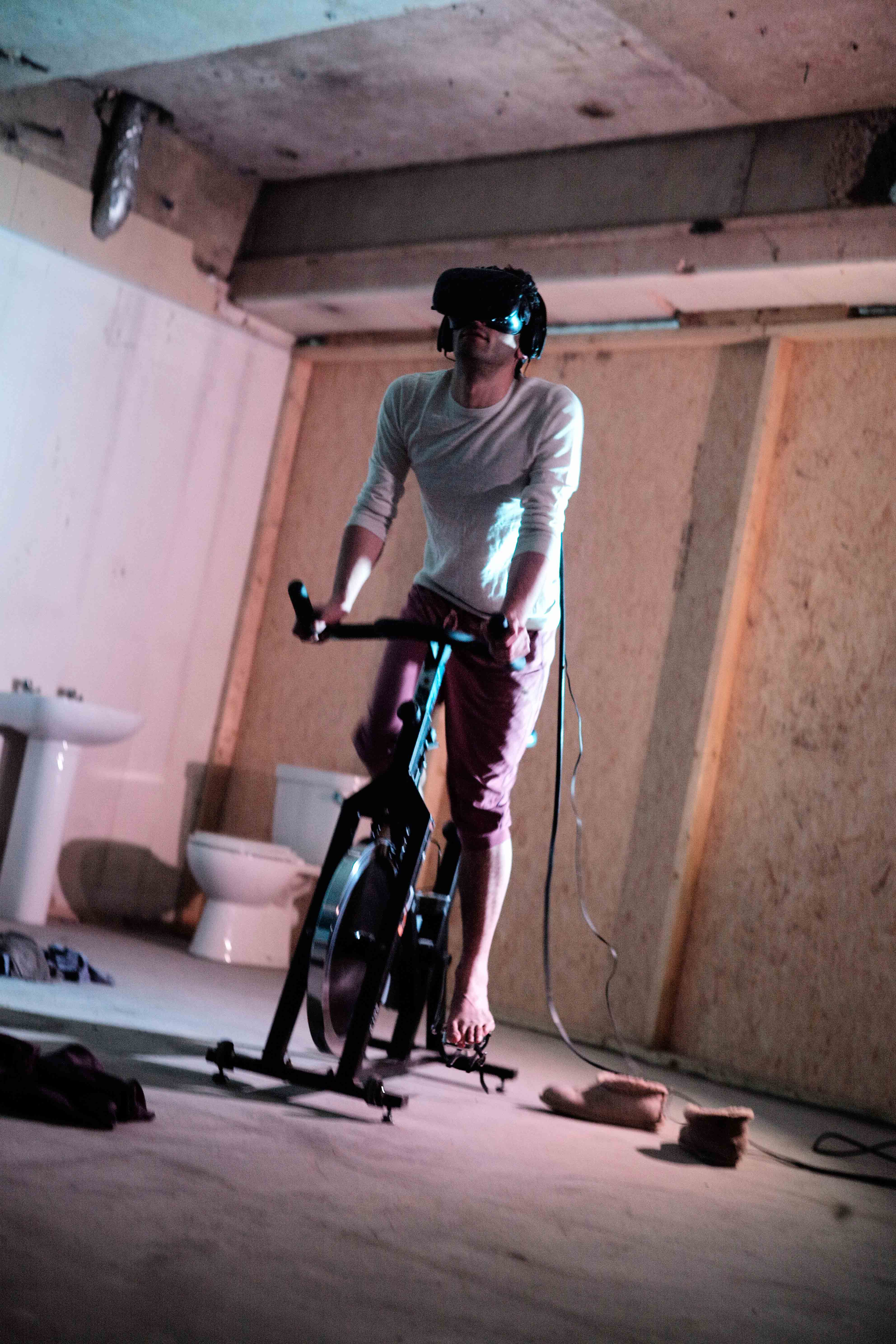 An action shot of the artist wearing the VR headset whilst using the exercise bike.