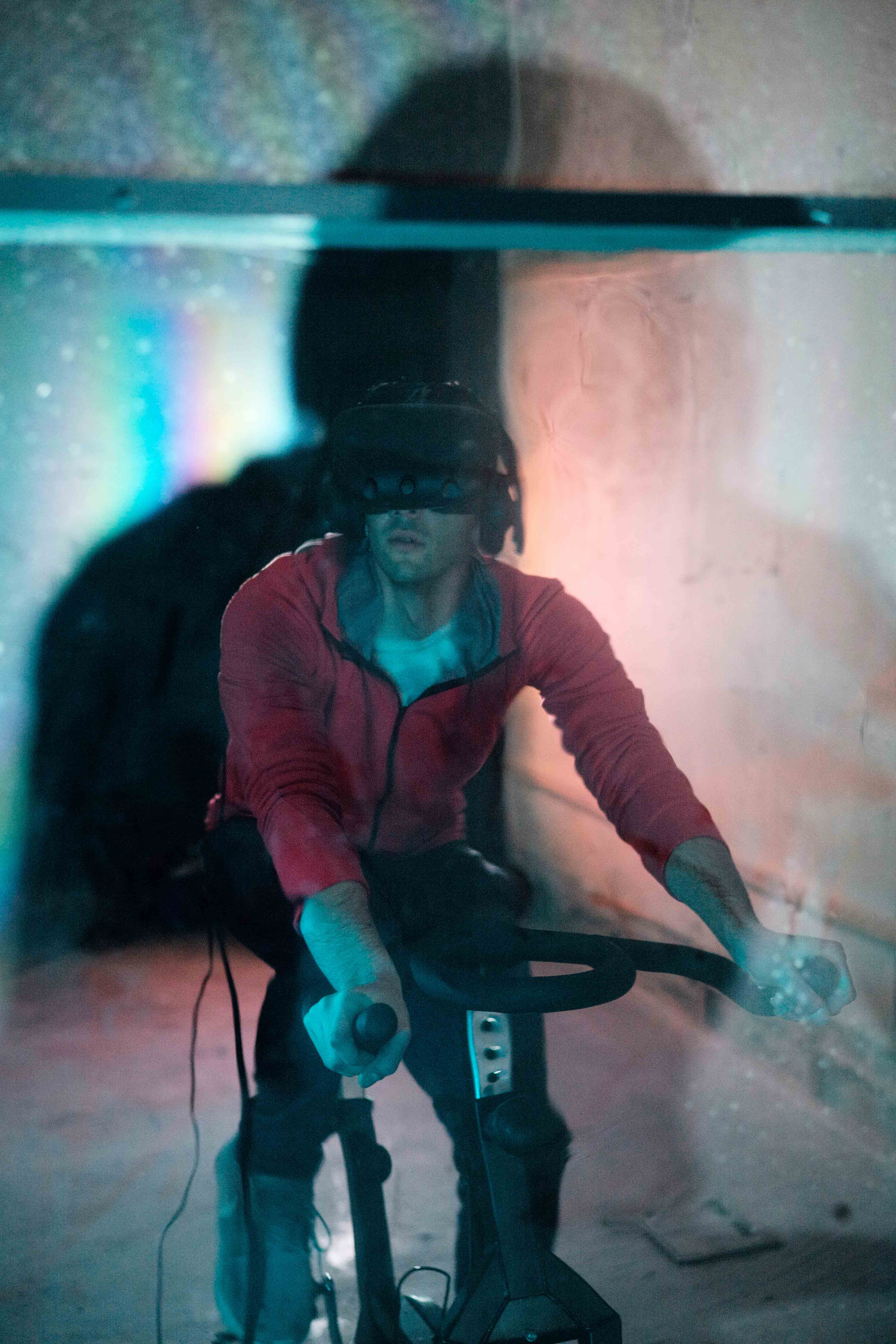 The artist wearing the VR headset whilst using the exercise bike.