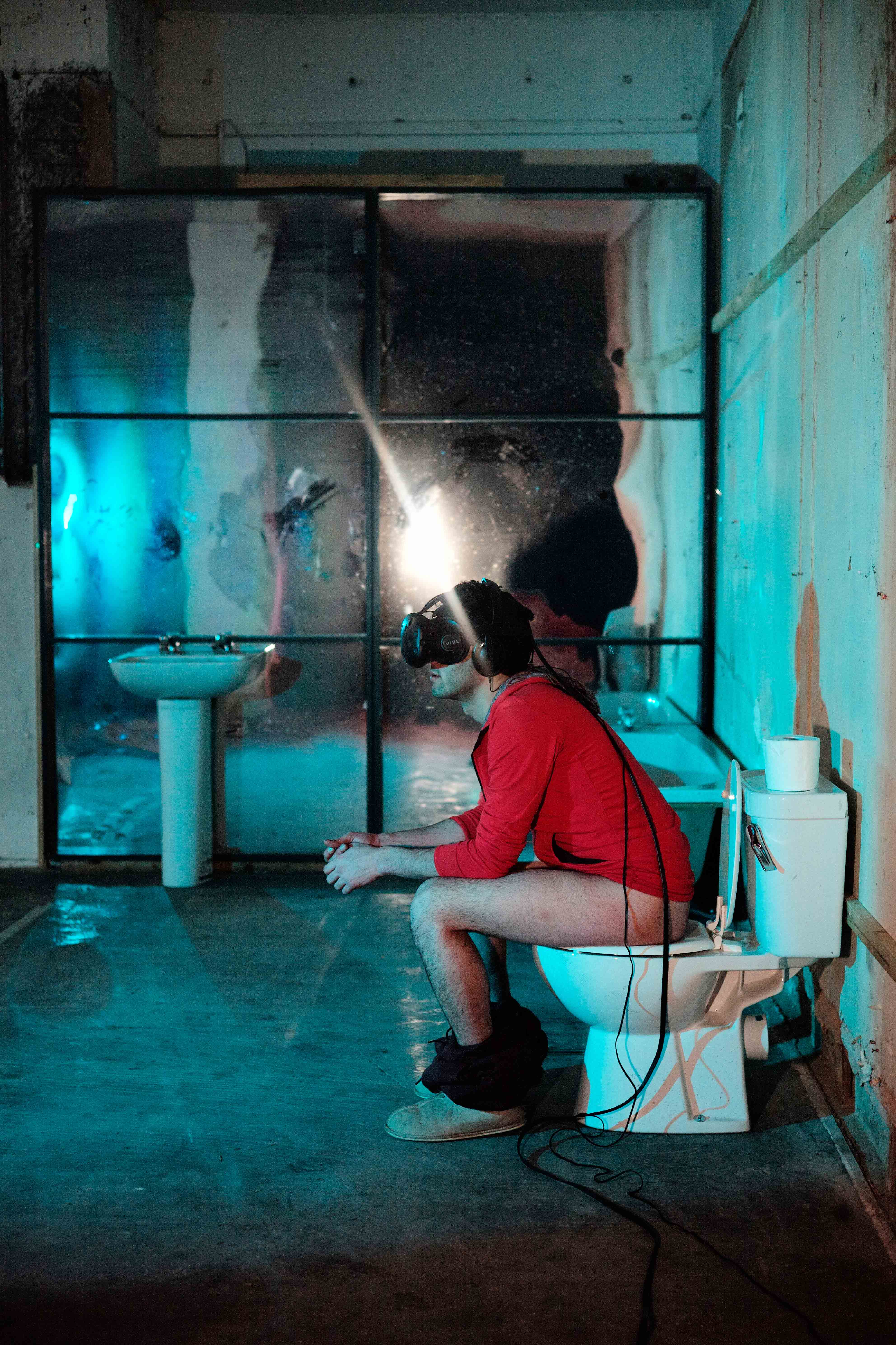 A side view of the artist wearing the VR headset whilst using the toilet.